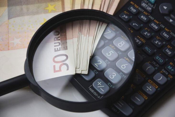 Lupa sobre dinero y calculadora
